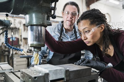 Two women wearing safety glasses standing in a metal workshop, working on metal drilling machine.