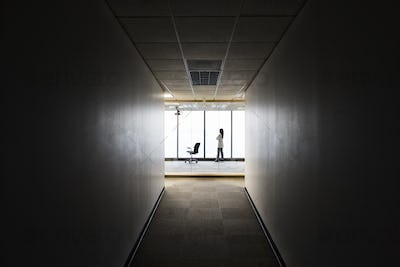 A businesswoman standing at a window at the end of a long hallway.