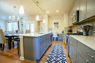 Modern home kitchen diner with green grey fitted units, a kitchen island and blue floor rug.