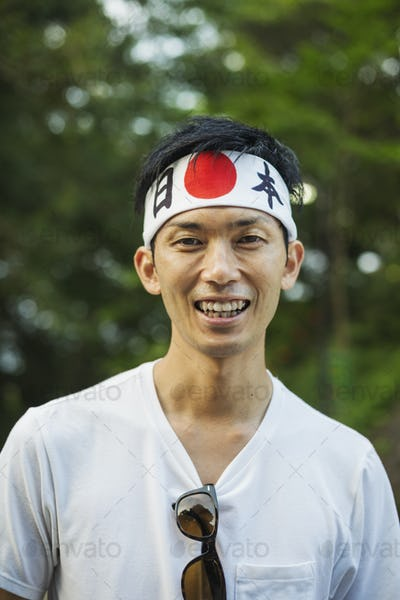 Portrait of man wearing headband  with Japanese flag smiling at camera.