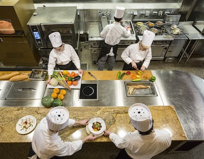 A view looking down on a crew of chefs working in a commercial kitchen,