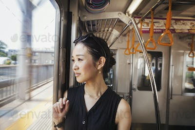 A woman on a moving train looking out of a large window.