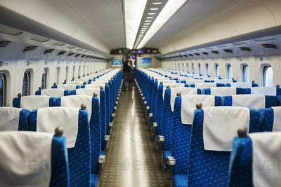 Interior view of passenger train carriage with blue seats, people in the background.