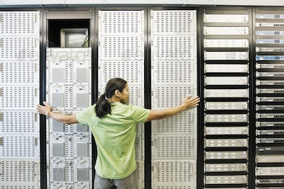 Computer technician working in a large computer server room.