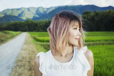 A young woman standing in open space by rice paddy fields of green shoots, and mountain landscape.