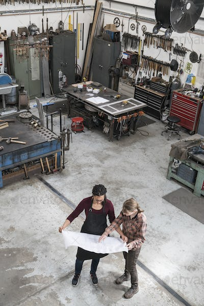 High angle view of two women standing in metal workshop, holding technical blueprint.