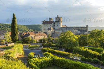 Landscape with trees, hedges and medieval castle with graveyard in the mid distance.