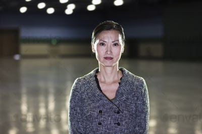 An Asian businesswoman  standing in a dimly lit and dark exhibition area in a convention center.