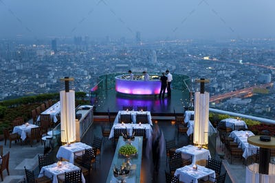 High angle view of rooftop restaurant on a skyscraper, illuminated cityscape in the distance.