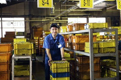Japanese man wearing baseball cap and blue overall standing in factory, yellow crates on shelves.