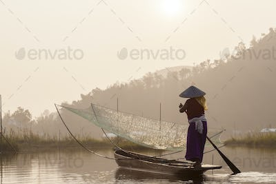 Fisherman on traditional fishing boat with net on a lake.