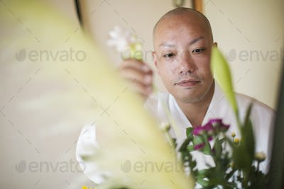 Close up of Buddhist monk with shaved head wearing white robe arranging flowers in a vase.