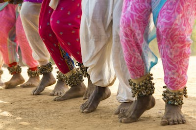 Low section view of barefoot dancers in a row on a street, wearing pink trousers and ankle bells.