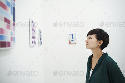 Woman with short black hair wearing green shirt standing in art gallery, looking at modern painting.