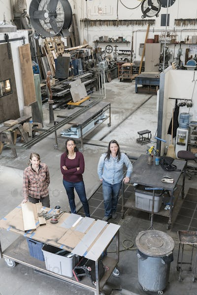 High angle view of three women standing in metal workshop, looking at camera.