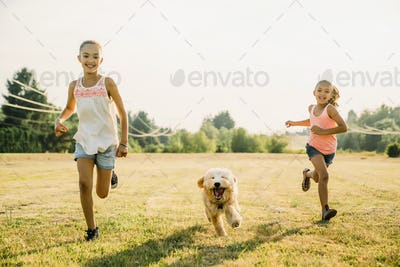Girls running through field with labradoodle puppy