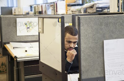 A Black man working in his cubicle in an corporate office.