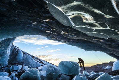 Side view of person climbing up on ice rock at the entrance to a glacial ice cave.