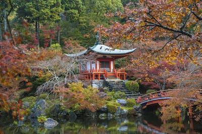 Park in autumn with traditional Japanese temple built on rocks, lake, bridge and trees.
