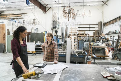 Two women standing at workbench in metal workshop.