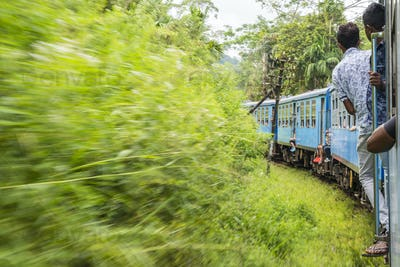 Train journey through lush forest, passengers standing in doors of moving blue train.
