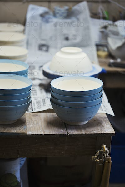 Close up white bowls with  blue glaze in a Japanese porcelain workshop.