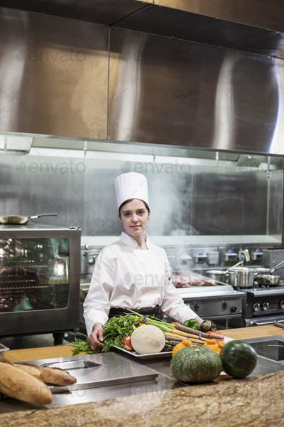 A young caucasian chef working with fresh vegetables in a commercial kitchen,