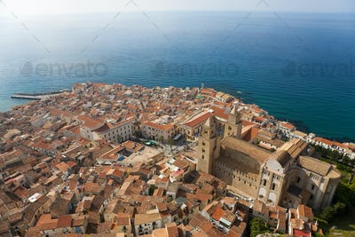 High angle view across rooftops of traditional houses and church in a city on the Mediterranean Sea.