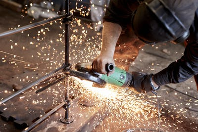 An artisan metalworker at work holding an angle grinder, workng on a metal fence.