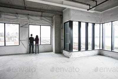 Two business owners standing in their new empty raw business space.
