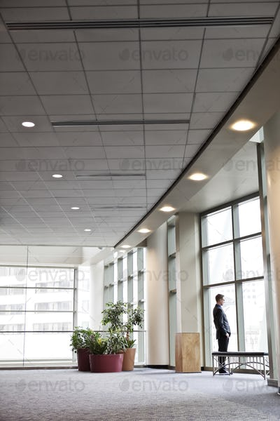 A businessman standing at a window in a large convention center lobby.