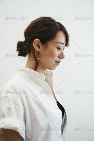 Profile view of woman with ponytail wearing white shirt standing in art gallery.