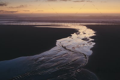 Landscape with stream flowing into ocean surf at dusk.