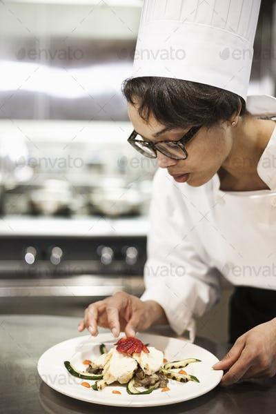 A black female chef working in a commercial kitchen,
