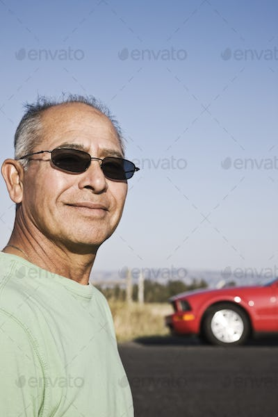 A portrait of a hip senior Hispanic male on a road trip.