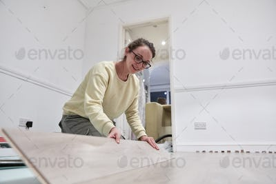 Woman fitting new wooden floor board