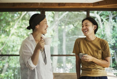 Man and woman standing indoors, holding coffee mugs, lookign at each other, smiling.