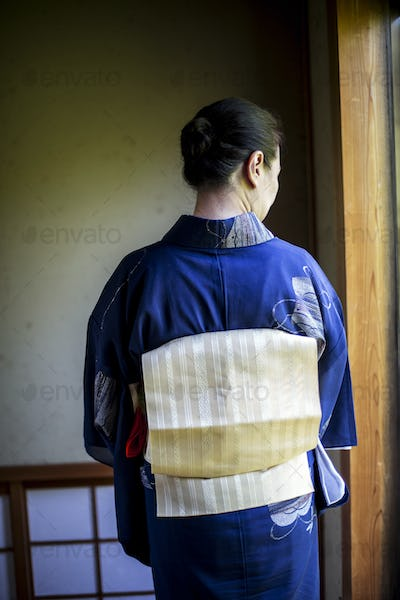 Rear view of Japanese woman wearing traditional bright blue kimono with cream coloured obi.