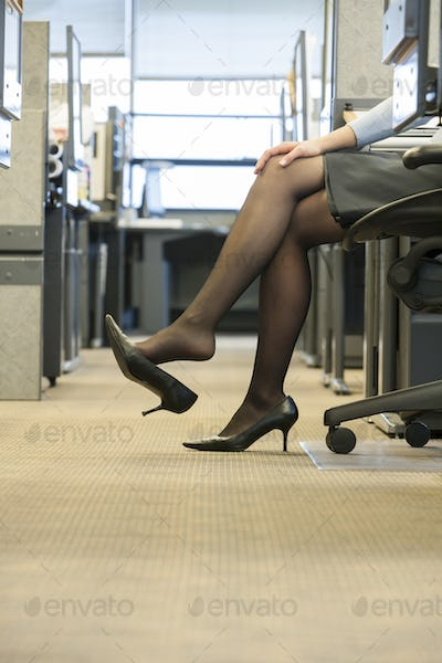 A closeup of a businesswoman's legs, skirt and shoes in a corporate office.