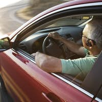 A senior Hispanic man at the wheel of his sedan with an ear piece for communications.