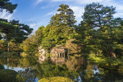 Landscape garden in autumn, with trees and pond, a boathouse in the distance.