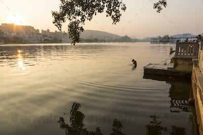 People swimming in a lake in early morning.