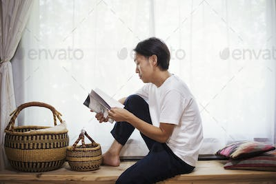 Man sitting indoors on a wooden bench with baskets, crossed legs, reading.