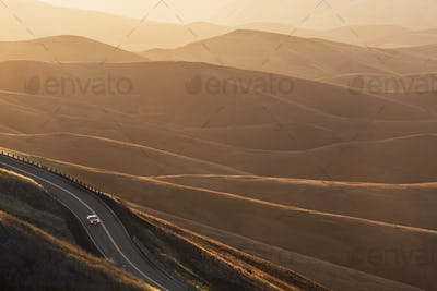 A view looking down of a car moving on a highway at sunrise near Lewiston, Idaho USA.