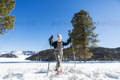 A six year old boy with snow shoes and ski poles