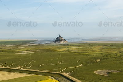Landscape with castle and monastery on a small island near the coast in the distance.