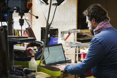 A craftsman at a desk in a workshop using a laptop computer on a cluttered desk.