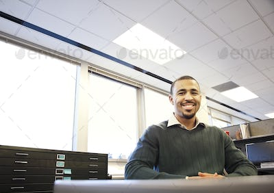 A portrait of a Black businessman in his corporate office.