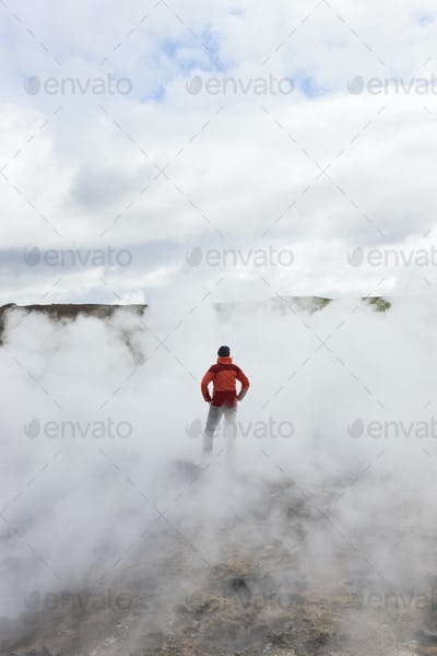 Rear view of woman standing by geothermal pools, surrounded by steam.