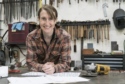 Blond woman wearing checkered shirt standing in metal workshop, looking at camera.